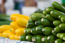 stack of green and yellow courgettes on a market stall