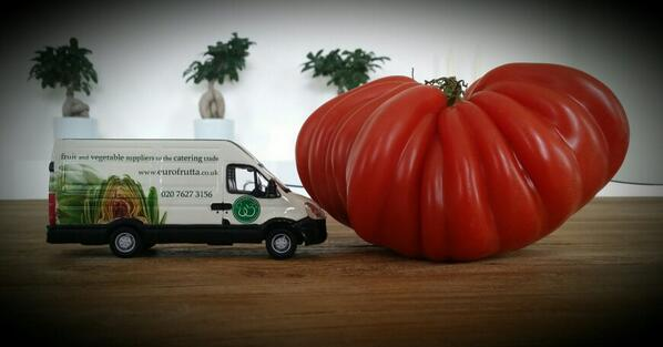 miniature van with Eurofrutta, fresh fruit and vegetable suppliers logo and big cour de beouf tomato on a wooden table
