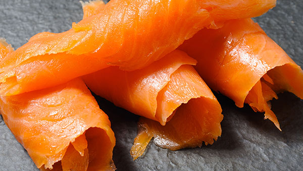 Close-up of rolls of smoked salmon on grey slate