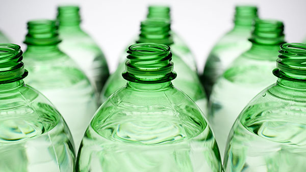 Plastic green bottles close up with water