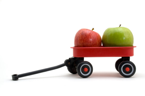 Green and red apple in a small red wagon.