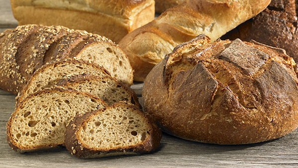 Several rustic loaves of bread warmly lit on a wood background.